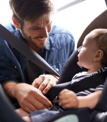 A cheery father buckles his child into a car seat.