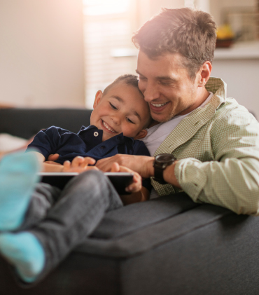A father snuggles with his son on a lounger chair and looks at a tablet.