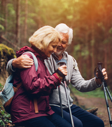 An elderly couple embrace each other as they take a rest on their hike through the woods.